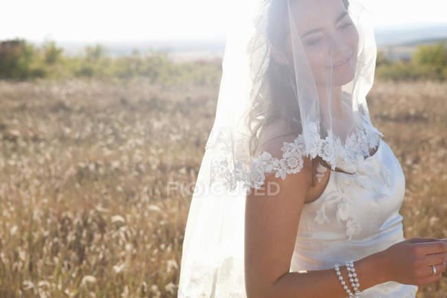 Novia recién casada de pie en el campo - foto de stock