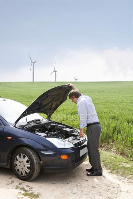 Людина з розбитою машиною на вітровій фермі. — стокове фото