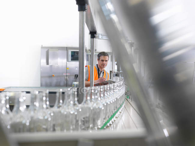 Factory worker examining bottles — Stock Photo