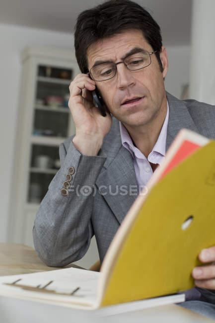 Homme mûr travaillant à la maison et utilisant le téléphone portable — Photo de stock