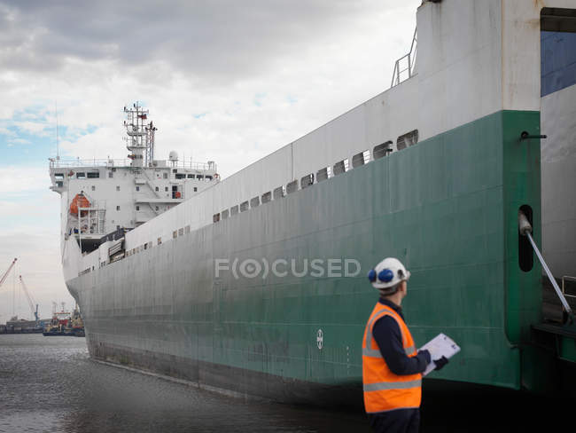 Trabalhador portuário olhando para navio recipiente — Fotografia de Stock