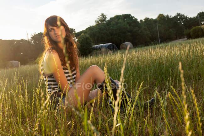 Женщина, сидящая на травяном поле — стоковое фото