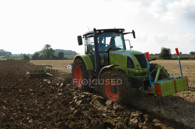 Farmer driving tractor through fields — Stock Photo