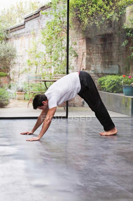 Man practicing downward dog yoga pose — Stock Photo