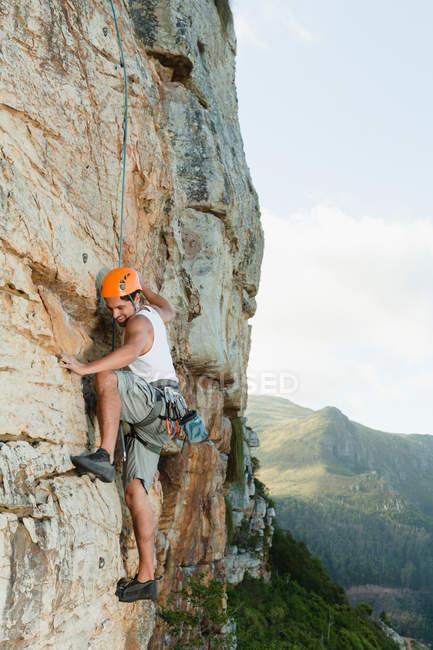 Climber scaling steep rock face — Stock Photo