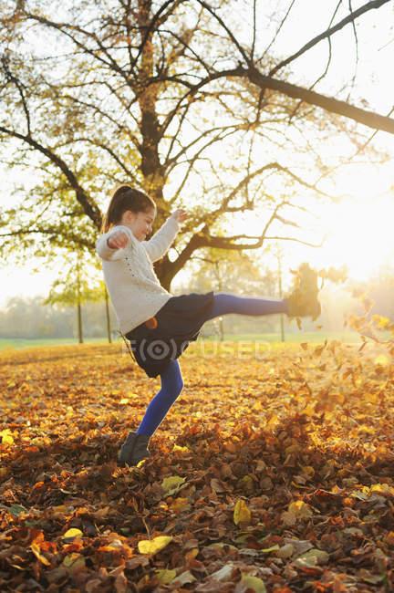 Lächelndes Mädchen beim Spielen in Herbstblättern — Stockfoto