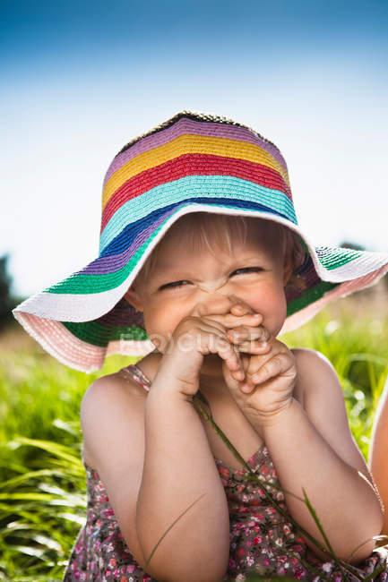 Toddler girl wearing sunhat in grass — Stock Photo