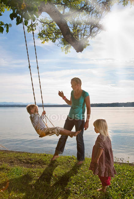 Mother playing with children on swing — Stock Photo