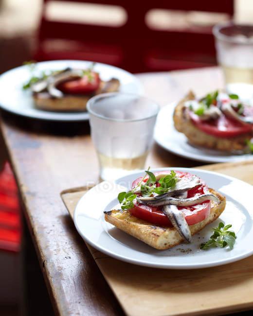 Bruschetta mit Sardellen und Tomaten Scheibe am Tisch serviert — Stockfoto
