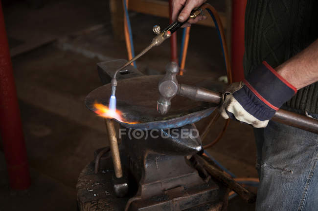 Blacksmith at work in shop, cropped view — Stock Photo