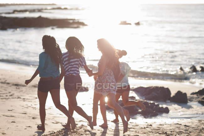 Женщины бегают вместе на пляже — стоковое фото
