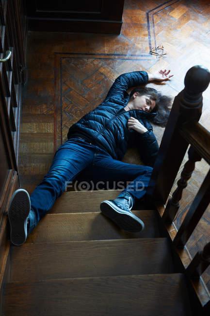 Adolescente acostado al pie de las escaleras - foto de stock