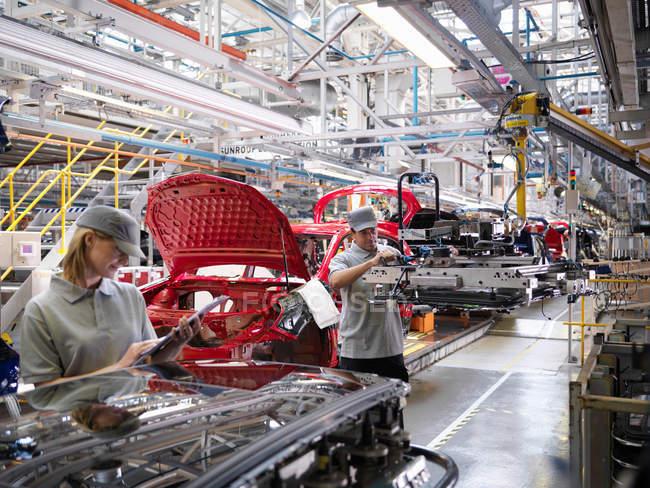 Trabalhadores da fábrica de automóveis na linha de produção — Fotografia de Stock