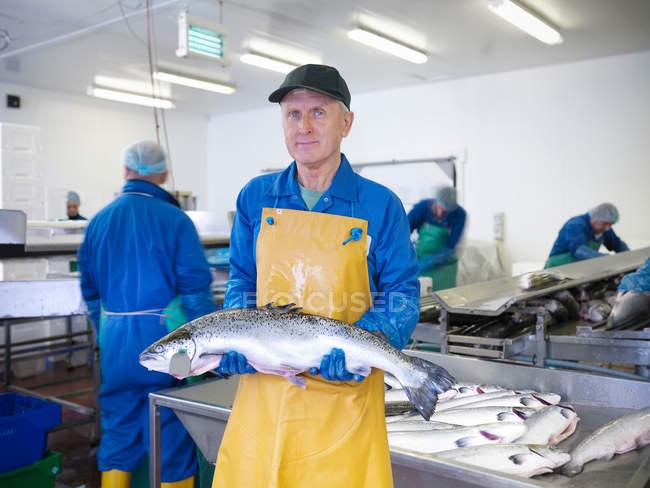 Портрет людини, що тримає свіжу руку вирощували шотландський лосось на заводі рибної ферми — стокове фото