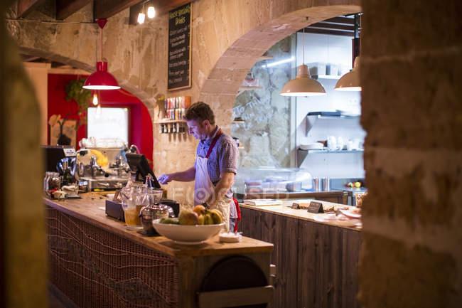 Restaurant owner working behind cash register — Stock Photo