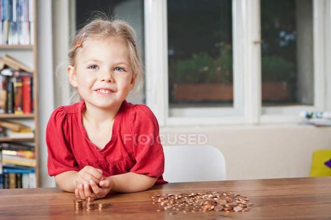 Дівчинка, граючи з копійки за столом — стокове фото