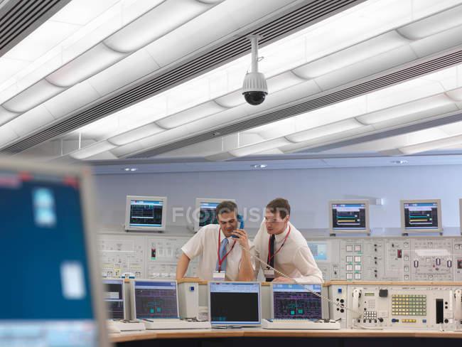 Operators on telephone in control room — Stock Photo