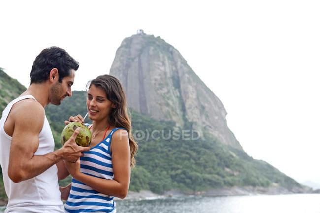 Pareja con cóctel en la playa, Montaña Sugarloaf, Río de Janeiro, Brasil - foto de stock