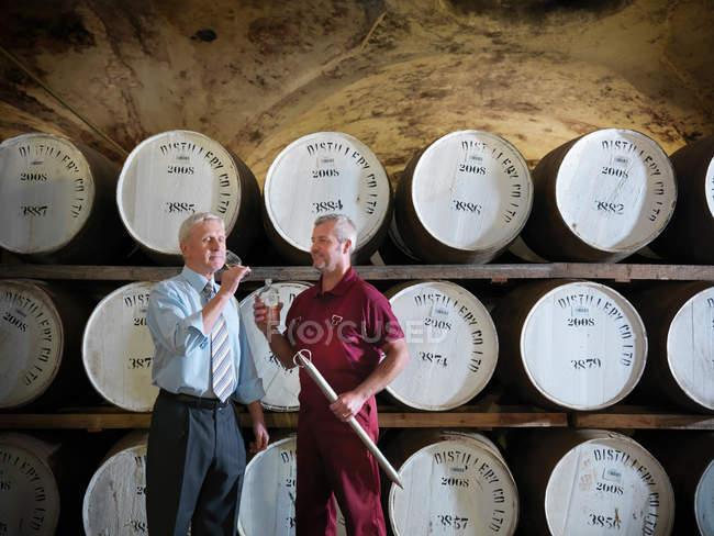 Travailleur avec échantillon de whisky à côté de barriques de whisky vieillissantes en distillerie — Photo de stock