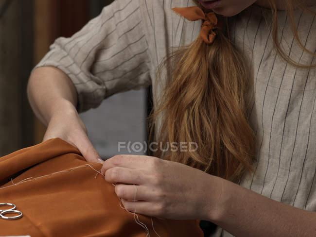 Обрезанный крупным планом молодых дизайнерских рук, шьющих оранжевую ткань — стоковое фото