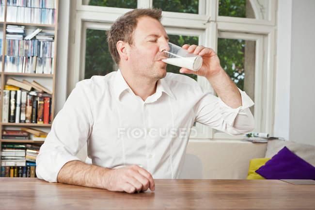 Homme buvant du lait à table — Photo de stock