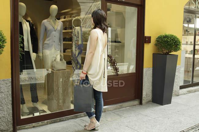 Женщина ищет в витрине бутика, Милан, Италия — стоковое фото