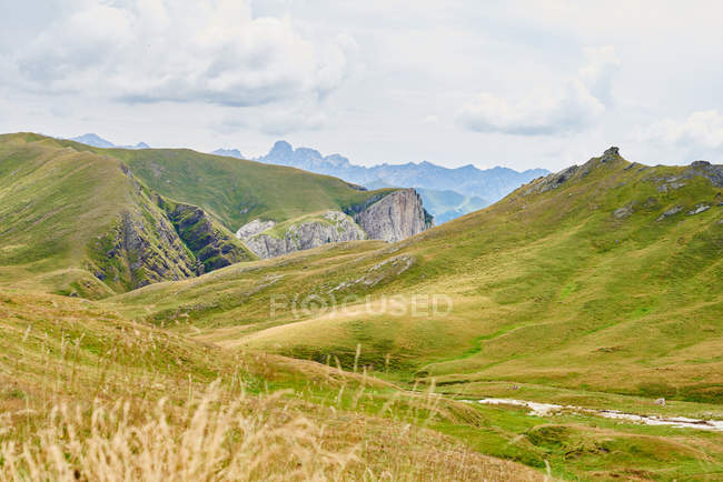 Scenic view of green mountains under cloudy sky — Stock Photo