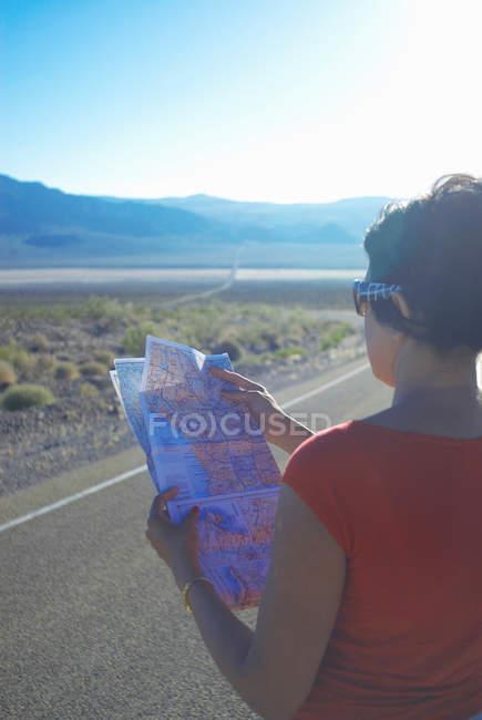 Mujer leyendo mapa en camino rural - foto de stock