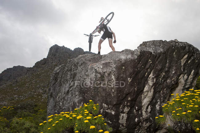 Young man carrying mountain bike on top of rock formation — Stock Photo