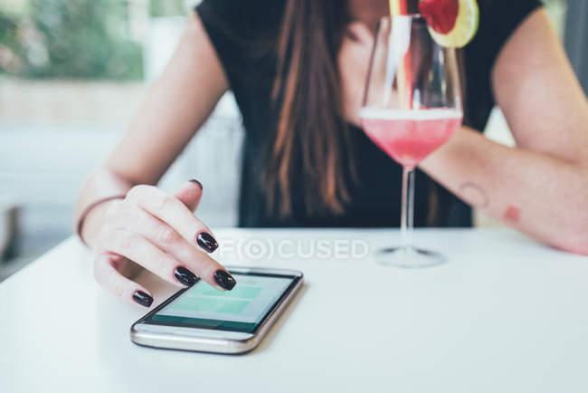 Куповані постріл молоду жінку на тротуарі кафе таблиці за допомогою сенсорного екрану смартфона — стокове фото