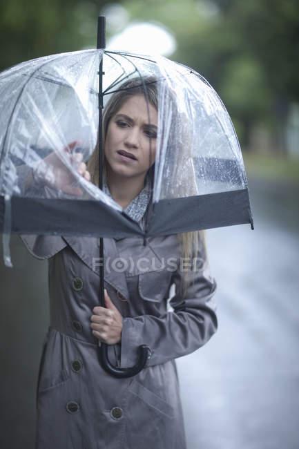 Молода жінка, дивлячись на дірку в парасолька — стокове фото
