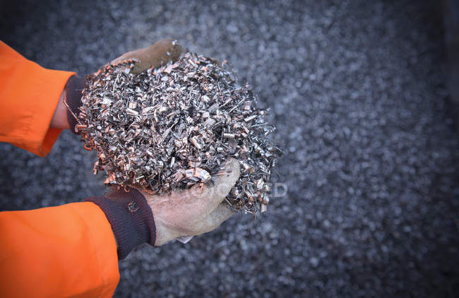 Close up of worker holding titanium turnings — Stock Photo
