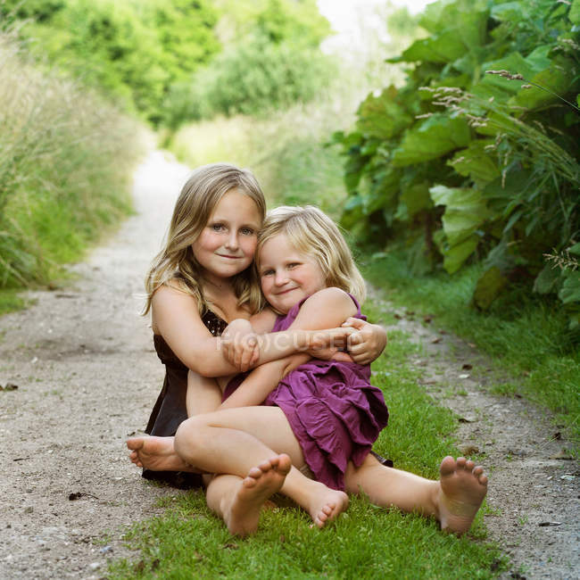 Girls hugging on dirt path, focus on foreground — Stock Photo