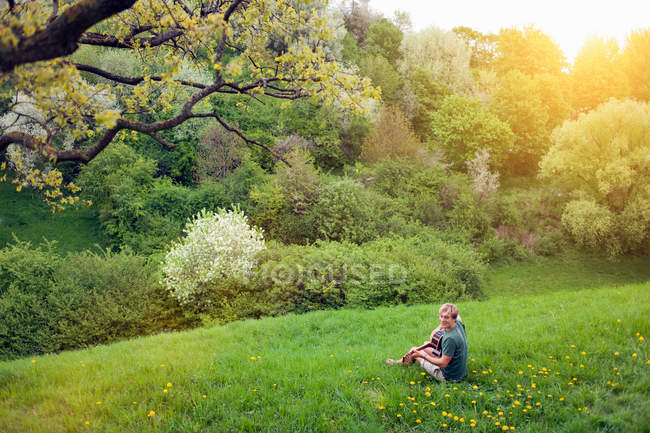 Distant view of young man sitting in field with guitar — Stock Photo