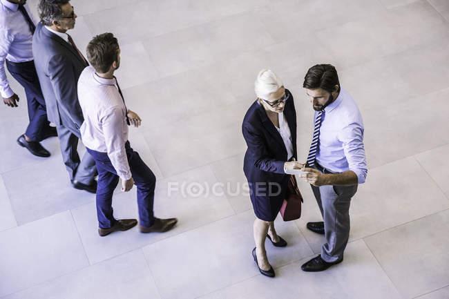 Високий кут зору двох бізнесменів і жінок, які читають смартфон в офісному атріумі — стокове фото