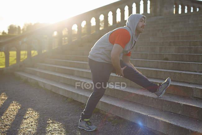 Молода людина, розтягування ногою крок — стокове фото
