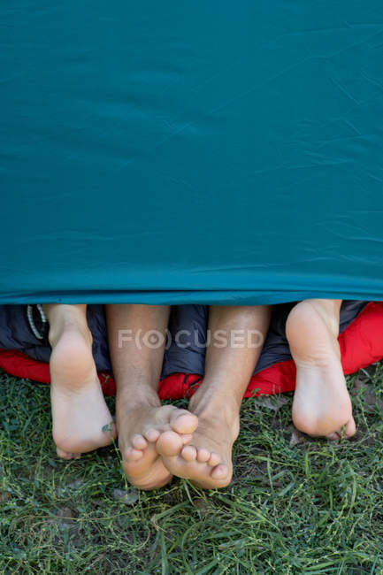 Two people feet sticking out of tent — Stock Photo