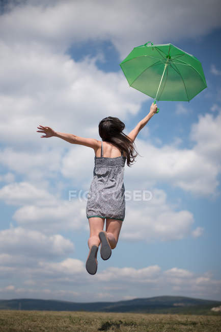 Rear view of mid adult woman holding green umbrella, jumping — Stock Photo