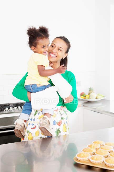 Мати і дочка сміятися в кухні — стокове фото