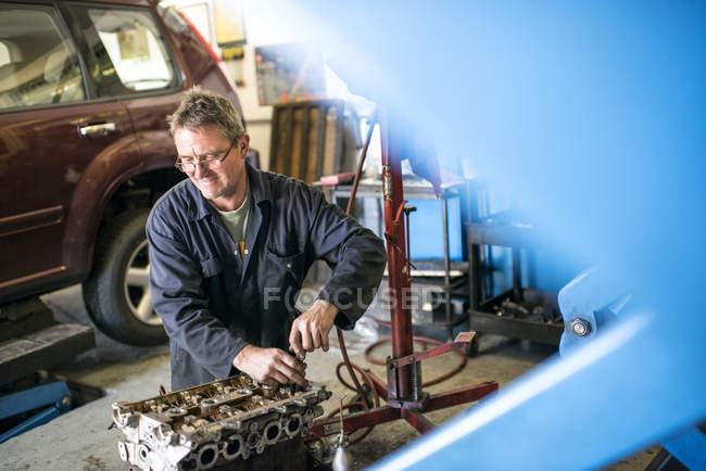 Meccanico di lavoro su parti di auto in garage — Foto stock