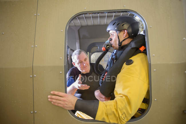 Offshore oil worker in simulated helicopter, being trained by tutor in sea ditching survival, in pool facility — Stock Photo