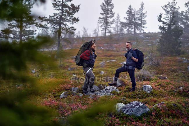 Due escursionisti sorridenti con gli zaini in viaggio, Lapponia, Finlandia — Foto stock