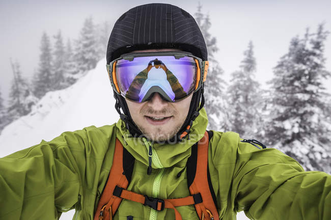 49378ae5457 Close up of male skier wearing ski goggles taking selfie on mountain at  Kranzegg