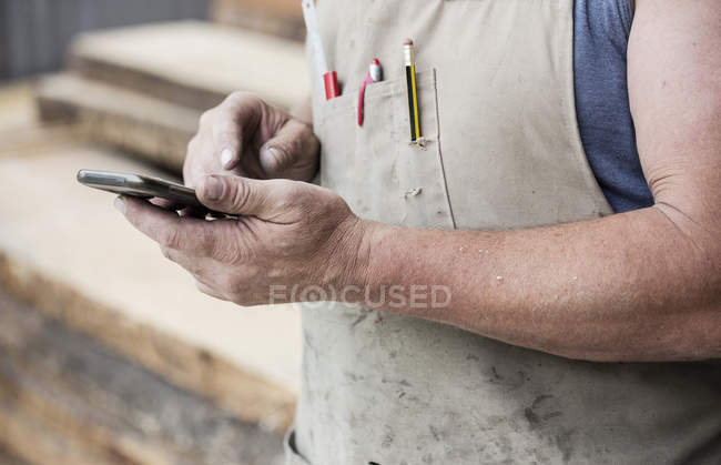 Carpenter in apron using cell phone, close-up partial view — Stock Photo