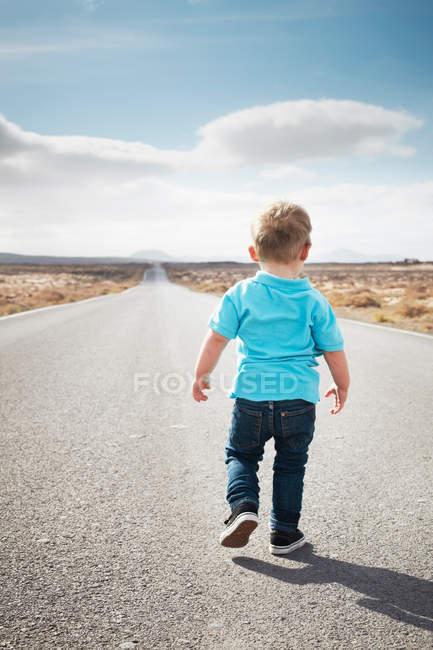 Мальчик ходит по асфальтированной сельской дороге — стоковое фото