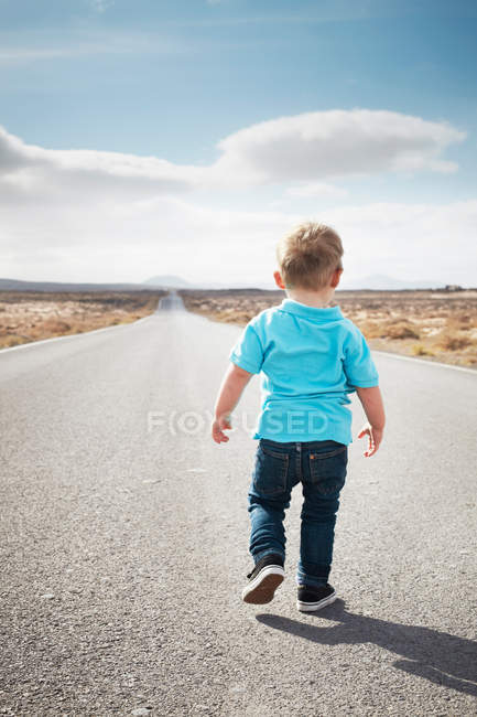 Boy walking on paved rural road — Stock Photo