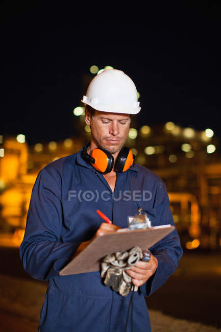 Worker with clipboard at oil refinery — Stock Photo
