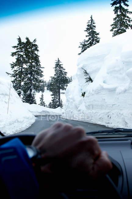 Человек едет по расчищенной дороге в снегу — стоковое фото