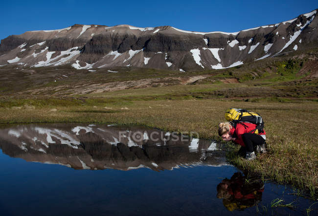 Hiker admiring reflection in still pond — стокове фото