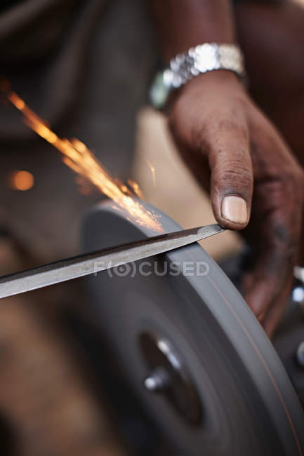 Close-up partial view of man sharpening tool — Stock Photo